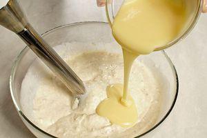 К бананово-творожной смеси влейте сгущенное молоко и еще раз хорошо взбейте блендером