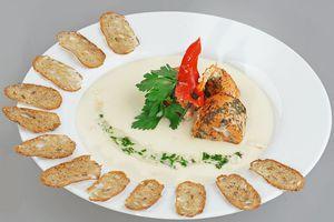 При подаче в тарелку налить кокосовый суп, сверху выложить рулетики из рыбы, украсить зеленью и гренками.