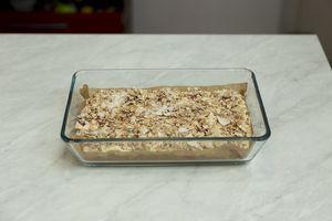 Приготовьте обсыпку: смешайте овсяные хлопья, сахар и кокосовые чипсы. Покройте ровным слоем обсыпки тесто.
