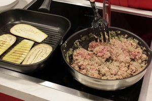 На разогретой с оливковым маслом сковороде обжарить лук и чеснок до прозрачности, добавить фарш, жарить еще 10 минут.  Одновременно на другой сковороде обжарить баклажаны с двух сторон до золотистого цвета, переложить на бумажное полотенце.