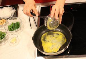 На разогретой с оливковым маслом сковороде обжарьте 2 яйца в течение 2 минут, посолите, поперчите по вкусу, отодвиньте на край сковороды.