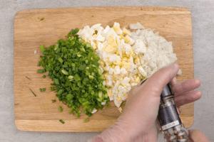 Лук репчатый мелко нарезать, зеленый лук и вареное яйцо порубить. Посолить, поперчить по вкусу.