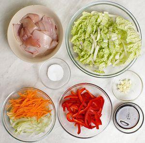 Капусту китайскую нарезать широкой полоской. Морковь, перец красный и лук нарезать тонкой соломкой. Чеснок мелко порубить.