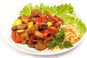 Выложить на тарелку гарнир, рядом мясо, украсить зеленью