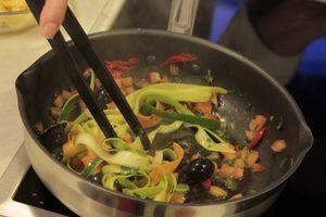 На разогретой сковороде с оливковым маслом обжарить чеснок, перец чили. Влить лимонный сок, добавить полоски моркови и цукини. Обжарить 1 минуту.