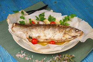 Готовую рыбу аккуратно раскрыть сверху (про скобы не забудьте и горячий пар), украсить дольками лимона, помидорами черри и веточками зелени.