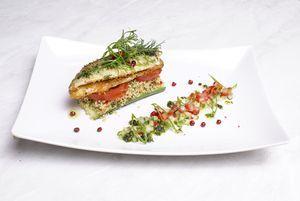Рядом с оформленным филе, полоской выложить нарезанные кубиком огурцы и помидоры, сбрызнуть соусом песто, украсить зеленым луком.