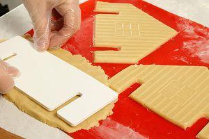 Раскатанное тесто вырезать по трафарету на силиконовом коврике или на пергаментной бумаге. В нижней части домика и стен нужно сделать прорези, чуть шире, чем толщина стен, чтобы удобнее было собирать