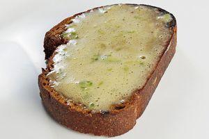 Поджаренный хлеб смажьте соусом, сверху выложите микс салатов, тонко нарезанные помидоры, бургер из тунца, полейте соусом.