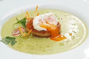 """В центр тарелки выложить """"башенку"""" из картофеля. Сверху положить яйцо (перед этим аккуратно снять пленку). По кругу налить крем-суп. Украсить свежими овощами."""