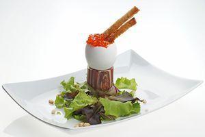Готовое яйцо установите в подставку для яиц, аккуратно ножом удалите верхнюю часть скорлупы. Украсьте красной икрой, кедровыми орехами, подсушенными гренками и листьями салата.
