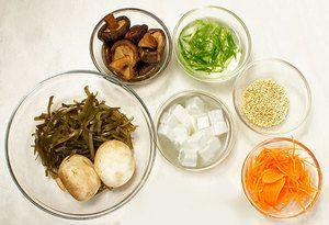 Водоросли вакаме или морскую капусту размочите в холодной кипяченой воде 15-20 минут. Морковь и лук зеленый нарежьте тонкой соломкой. Творог тофу нарежьте небольшими кубиками. Грибы шиитаки размочите в теплой воде 1-2 часа, затем слейте воду, залейте свежей водой и проварите 20-30 минут. Грибы шампиньоны промойте и нарежьте тонкими пластиками.