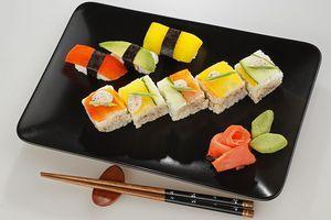 Выложите готовые суши на тарелку, украсьте имбирем и васаби.