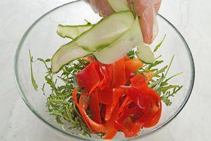 Отдельно в салатнике смешать салат руккола, нарезанные огурцы, помидоры и перец.