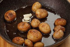 Пока рыба маринуется, обжарить картофель черри на смеси растительного и сливочного масла и парой долек чеснока.