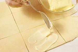 Разрежьте на прямоугольники примерно 10*10см. Смажьте мягким сливочным маслом
