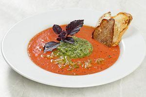 В центр тарелки выложите зеленое пюре с помощью кулинарного кольца, вокруг налейте гаспачо. Украсьте веточкой базилика и гренками. Можно добавить несколько капель соуса табаско. (можно просто смешать томатный суп с огуречным пюре)