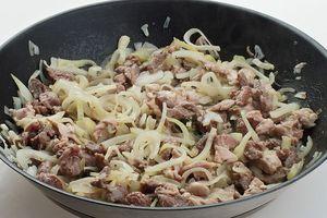 В это время на разогретой с растительным маслом сковороде обжарить нарезанное тонкой соломкой мясо и лук, до золотистого цвета. Накрыть крышкой и потушить 10-15 минут.
