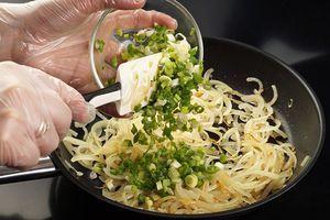 На разогретой с растительным маслом сковороде обжарить нарезанный соломкой репчатый лук до золотистого цвета. Снять с огня. Затем добавить мелко нарезанный зеленый лук.
