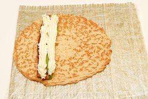 Аккуратно выдавите поверх угря и авокадо две полоски сливочного сыра с помощью кулинарного шприца или пакета