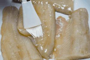 Филе судака разморозить естественным способом на нижней полке холодильника, обсушить бумажным полотенцем. Проверить на наличие крупных костей, удалить их пинцетом, если есть необходимость. Разрезать на порционные кусочки, сбрызнуть растительным маслом.