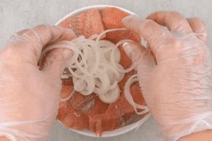 На картофель уложить филе рыбы, посолить, поперчить по вкусу.  Выложить тонкие колечки лука