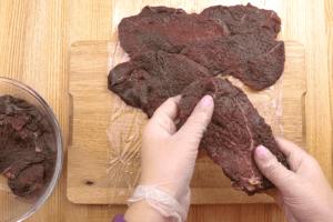 Подготовленное мясо разложить на пищевой пленке в один слой, прямоугольником, чтобы можно было завернуть в рулет.  Если какие то кусочки получились толстоваты, еще раз отбить их.