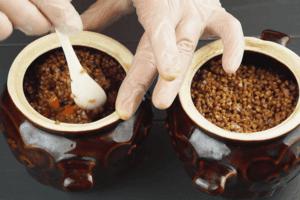 Затем добавить гречку, перемешать. Залить водой, чтобы она покрывала продукты на 1,5 см. Закрыть горшочки крышками.