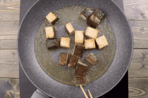 Тофу нарезать небольшими прямоугольниками. Обжарить на смеси растительного и кунжутного масла на хорошо разогретой сковороде до золотистой корочки. Переложить на бумажное полотенце.