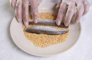 Корюшку разморозить естественным способом на нижней полке холодильника. Промыть, отрезать голову, разрезать рыбу на 2 части. Срезать кости. Должно получиться чистое филе на коже без костей.  Обмакнуть филе в смесь: мука панировочная, соль, специи