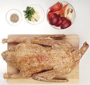 Замаринованного гуся достаньте из маринада. Яблоки и сливу нарежьте крупными дольками. Чеснок очистите и раздавите слегка ножом.