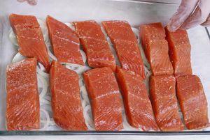 Лук нарезать кольцом, выложить слоем в форму для запекания. На лук уложить порционные кусочки рыбы.