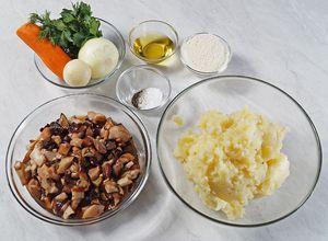 Сварите очищенный картофель в подсоленной воде до готовности, разомните в однородное пюре. Грибы разморозьте естественным образом на нижней полке холодильника, промойте, нарежьте небольшими кубиками.