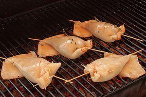 Затем обжарьте на разогретом гриле с двух сторон нафаршированные кальмары, по 3-4 минуты с каждой стороны.