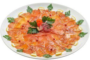 Нарежьте замороженное филе слабосоленого кижуча тонкими пластиками, выложите по всей поверхности тарелки тонким слоем. Сбрызните оливковым маслом, украсьте специями, дольками лимона и веточками зелени.