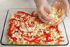На креветки выложить слой тонко нарезанного красного перца. Сварить яйца, часть белков отложить на оформление. Остальную часть натереть на крупной терке и выложить на перец.