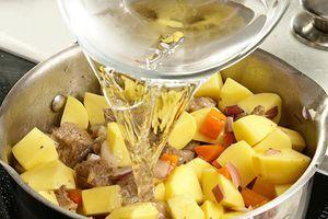 К мясу добавить картофель, немного посолить, поперчить, обжарить 10-15 минут, влить горячую воду. Тушить до готовности мяса и картофеля.