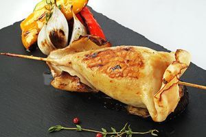 Украсьте готового кальмара овощами гриль, смажьте ароматным маслом.