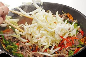 Следом положить куриные желудки, нарезанные соломкой и капусту. Обжарить еще 1-2 минуты.