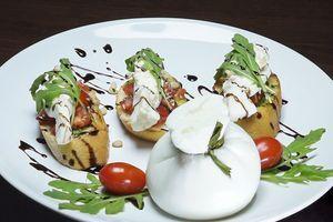 Каждую брускетту украсить салатом руккола, поперчить свежемолотым черным перцем. Сбрызнуть соусом крем-бальзамик